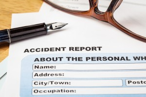 Accident report application form and pen on brown envelope and e